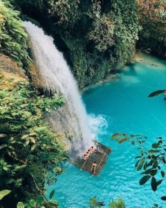 Looking down on waterfalls into aqua blue water surrounded by green forest