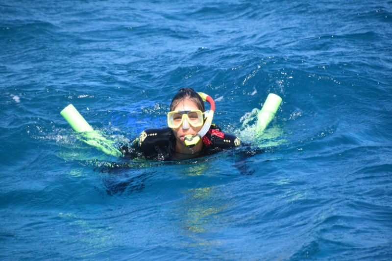 A lady enjoying snorkelling in crystal blue waters off the coast of port douglas