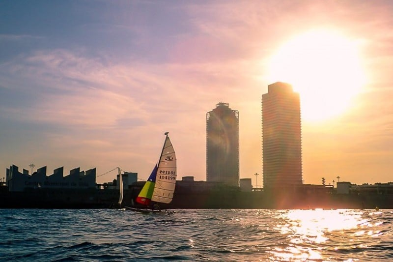 Pink sunset sky with skyscrapers in the background, with a sailing boat on the water