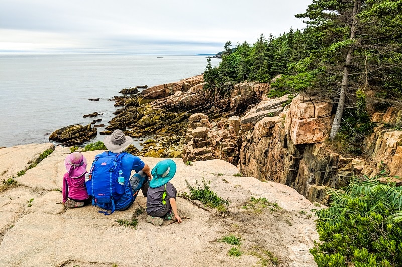 Man with 2 children sitting on a flat rock ledge looking out onto Acadia National Park