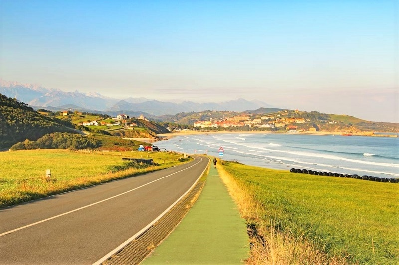 Long road stretching out in front, grass either side. leading to a beach