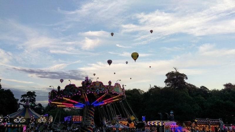 Hot air balloons i the air above a fairground