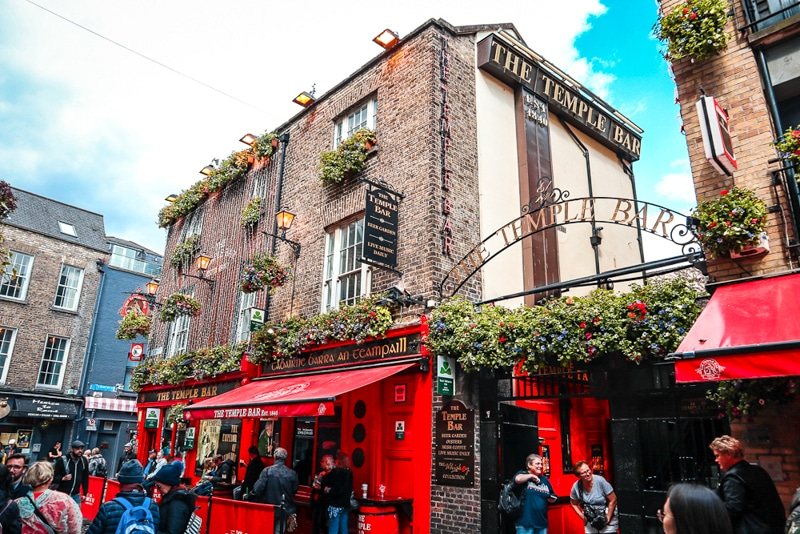 People milling about outside of Temple Bar - brick building with red awning