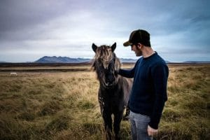 Man wearing a cap stroking an Icelandic pony