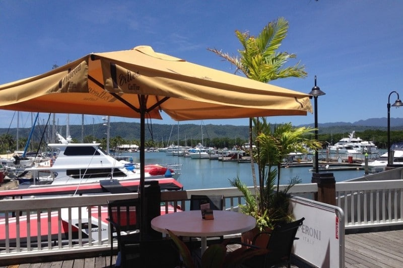 Restaurant umbrella over a table overlooking a harbour