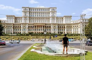 Large regal building with a fountain in the front and a man satnding by it