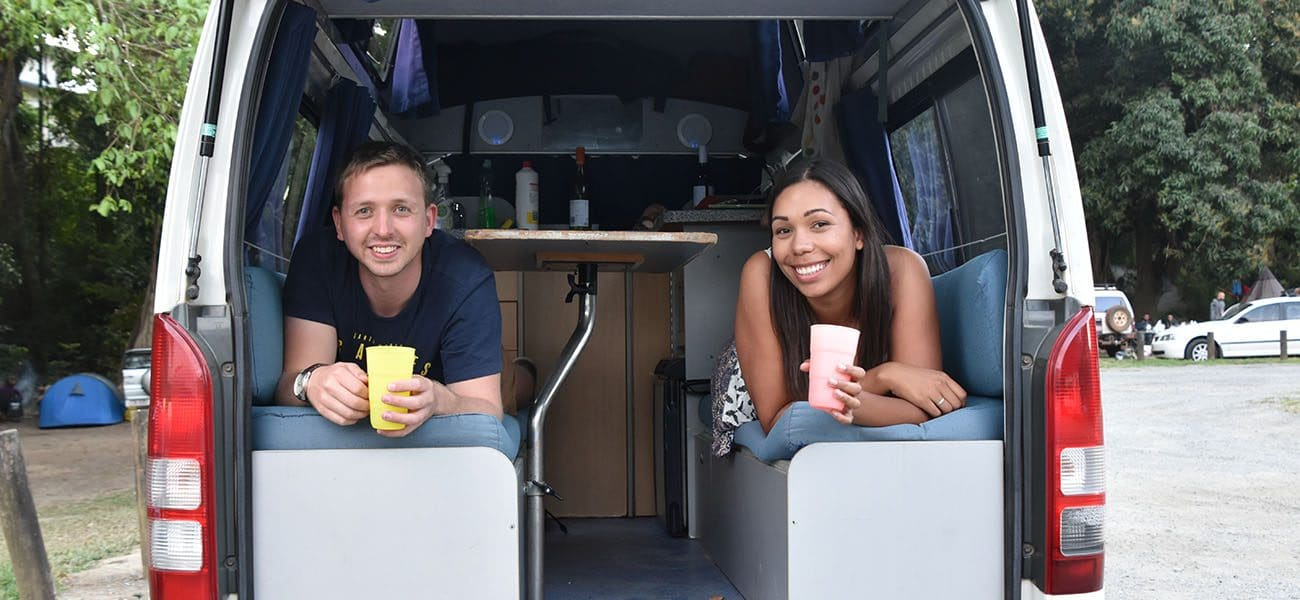 2 people in the back of a campervan smiling at the camera
