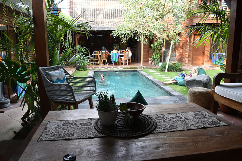 The view from a table of a pool and beautiful architecture in Bali.