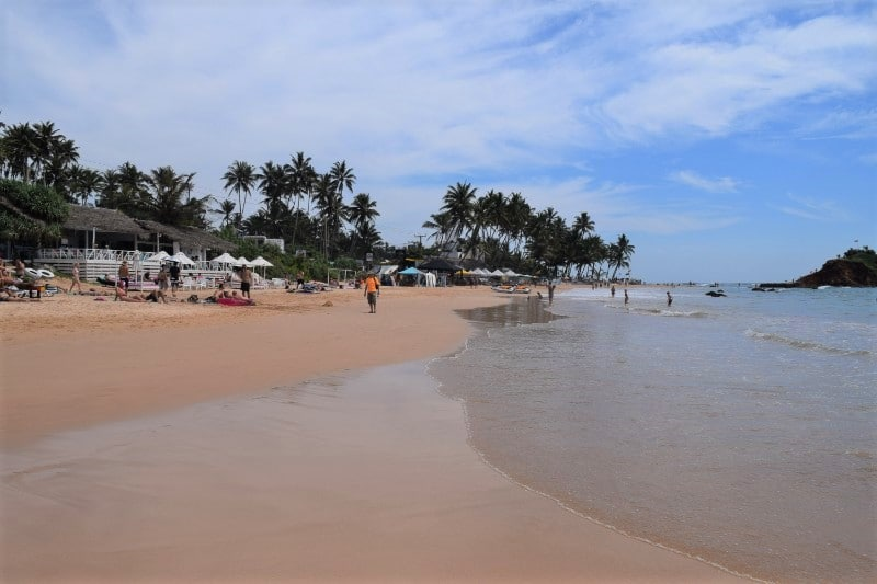 View of the sandy beach in Mirissa from the water's edge with some restaurants