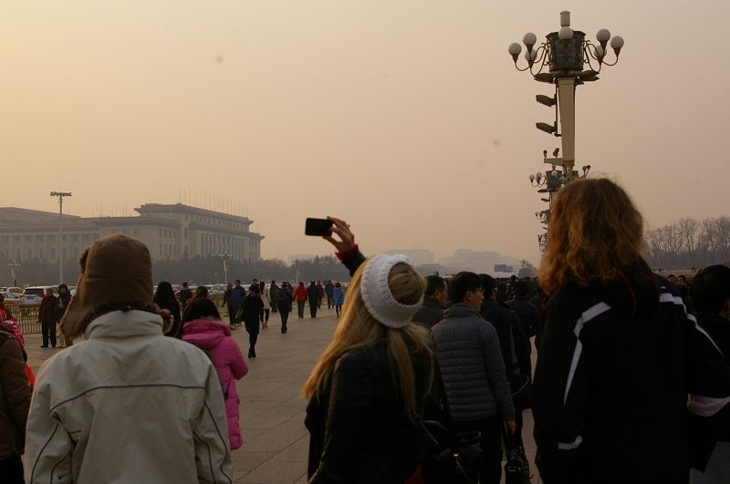 A group of people taking pictures of the forbidden city whilst the pollution is extremely bad