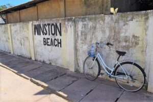 A bicycle with a water bottle in the basket, leaning against a yellow wall which ha the words Winston Beach on it