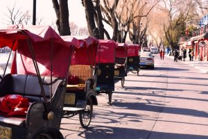 A line of peddle tuk tuks along a lake in China, pictured whilst backpacking in China