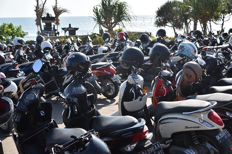 Many motorbikes in rows by the see in Bali