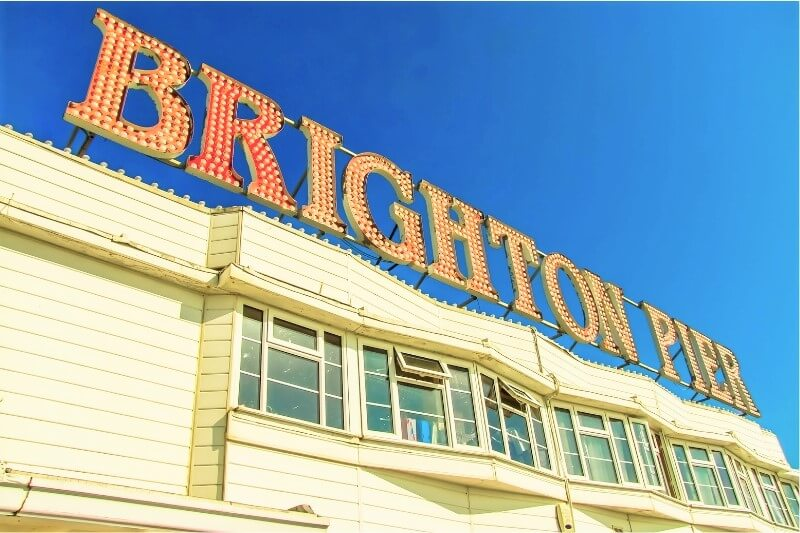 White building with orange words spelling out BRIGHTON PIER on the top