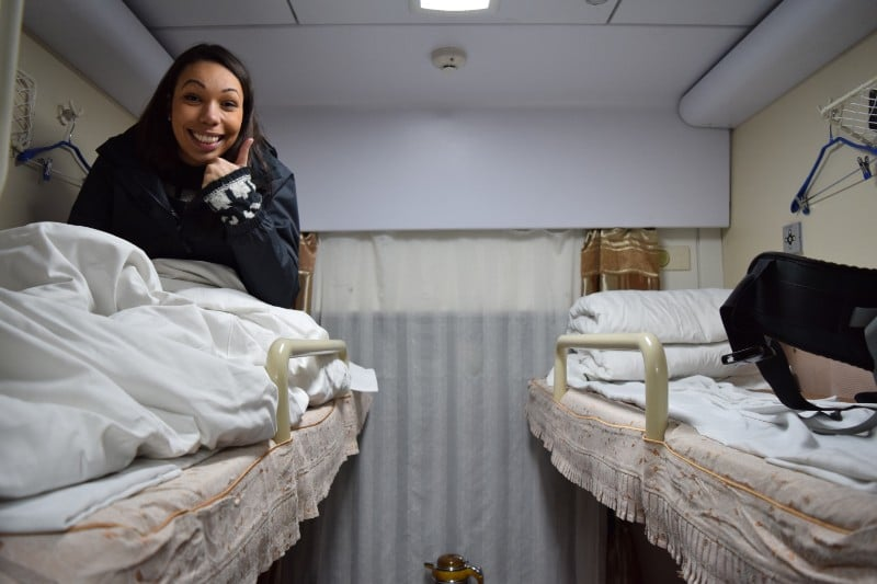 A lady doing a peace sign on the top bunk of a soft sleeper train in China