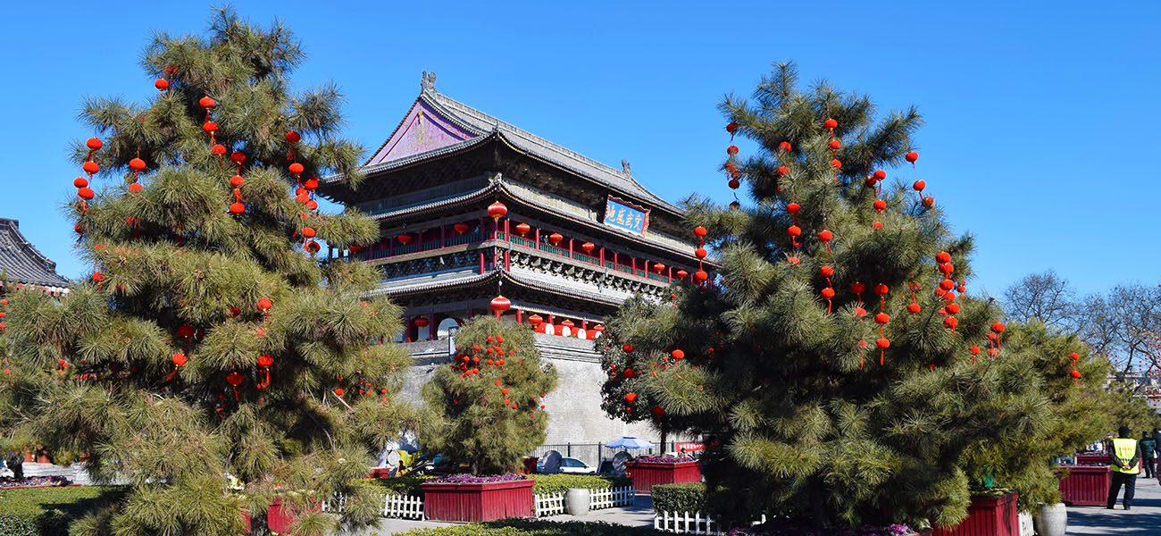 The drum tower in Xian with trees and red lanterns, pictured whilst backpacking china