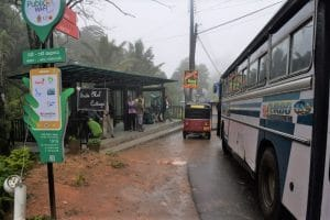 A white and blue bus on the side pulling up to a bus stop with a red tuk tuk next to it