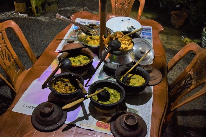 6 types of curry in clay pots with ladles on a table