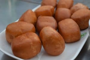 Lots of deep fried dough balls served with condensed milk