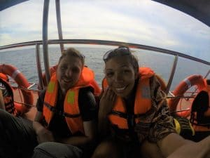 A woman and a man wearing orange life jackets sat on a boat taking a selfie