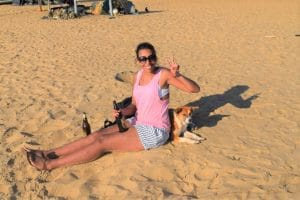 A girl sat on the beach making th epeace sign with a brown dog lying in the shade behind her