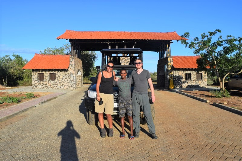 A woman and two men standing close together in front of the entrance to Yala National Park