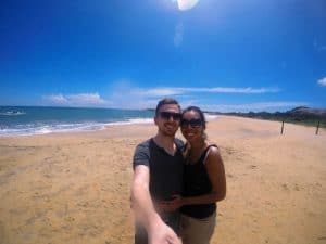 A man and a woman taking a selfie on an empty beach with clear blue skies