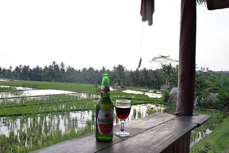 A beer and a glass of wine on a table overlooking some rice paddies full of water
