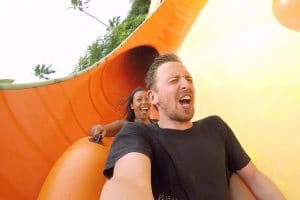 2 people coming down an orange slide at waterbom bali on day 6 of the 1 week bali itinerary
