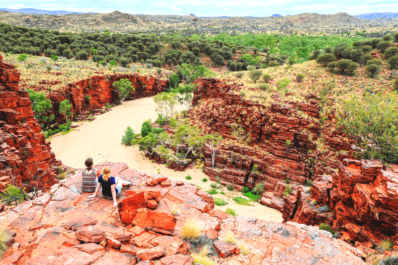 A man and a lady sat on a red rock overlooking the outback