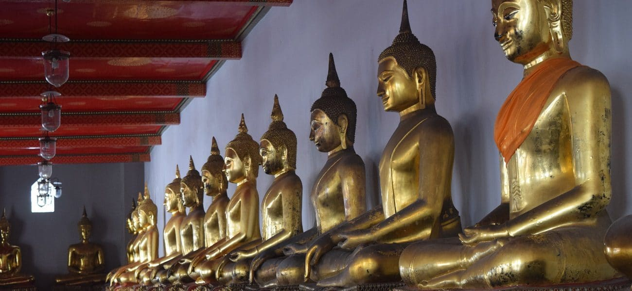 A row of golden buddahs and a bangkok temple