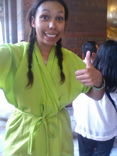 A lady smiling wearing a green overall in a temple in thailand