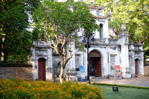 Old white building in Hanoi with tree in front