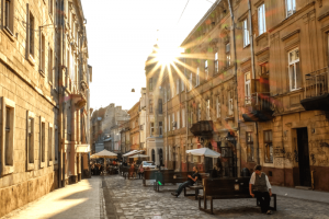 The sun shining behind a stone building onto a cobled street with restaurants and cafes