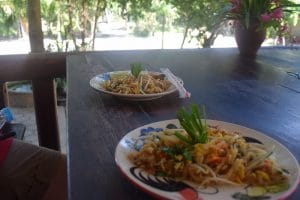 2 Plates of Pad Thai on a dark wooden table . Pictured in Chiang Mai whilst backpacking through Thailand