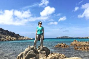 Lady standing on rocks in Sardinia. Visit Sardinia in September