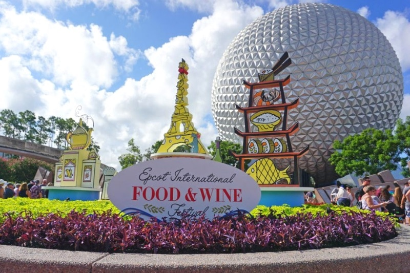 Gigantic golf ball and model of the Eiffel Tower behind the Epcot food and wine sign