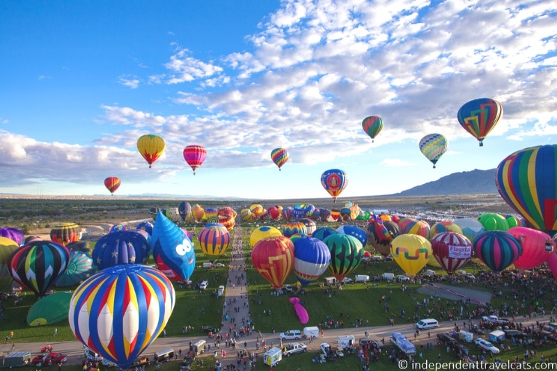 Tens of colourful hot air balloons in the sky over greenery