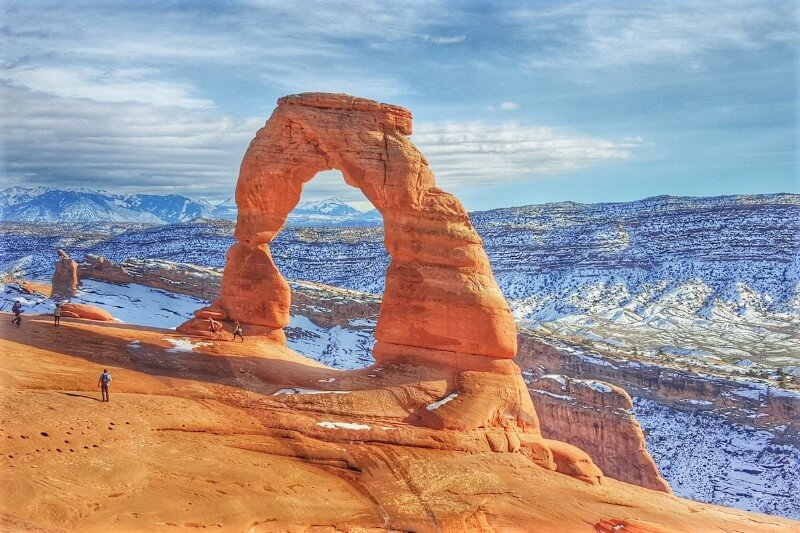 Red rock arch with mountains in the background