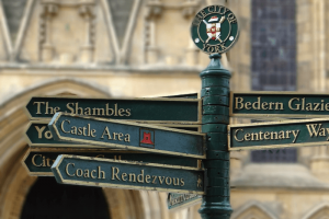 Green signpost in York in September with the word 'Shambles', 'Castle Area', 'Coach Rendezvous', 'Bedern Glaziers' and 'Cenetary Way''