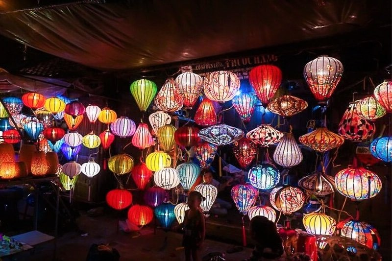 Tens of brightly coloured lanterns hanging in a building