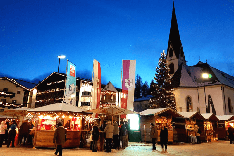 A tall church steeple at nighttime with Christmas market stalls in the foreground, in Austria - one of the best places to visit in December