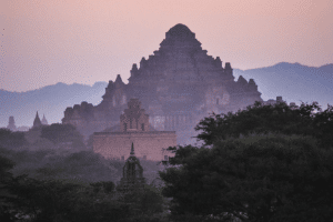 A temple in the background with foggy red sky and trees in front in Bagan - one of the best places to visit in December