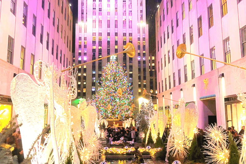 Large Christmas tree with bright multi coloured lights in front of tall building lit with pink in New York - one of the best places to travel in December
