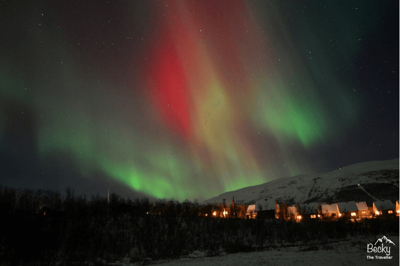 Red, yellow and green Northern Lights across the dark sky with village underneath