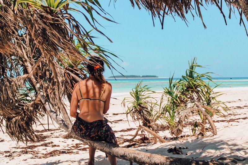 Girl sat on tree facing towards ocean in Zanzibar in Deceember