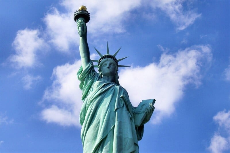 Statue of Liberty from low angle with blue skies and cloud - New York is one of the best places to visit in December