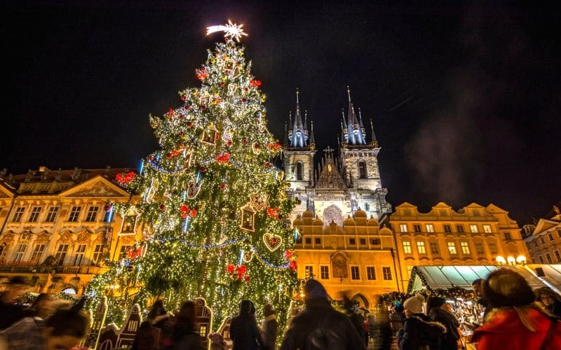 Huge city Christmas tree in Prague with church building in background