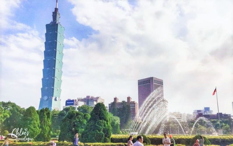 Tall skyscraper in background, park in foreground with fountains and green trees