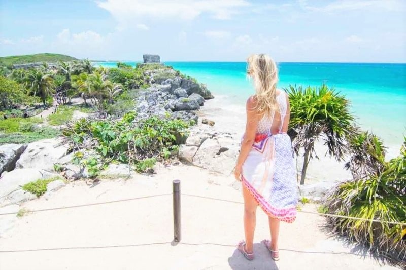 Blonde woman facing away from the camera looking out into blue sea and green shrubbery